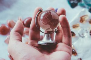 a hand holding a small globe to represent relocating in big 4 accounting firms