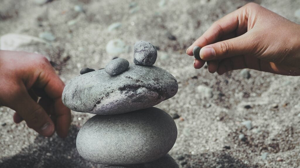 A person balancing rocks to symbolise building trust on social media