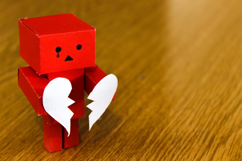 a paper robot holding a broken heart to symbolize the biggest networking mistakes
