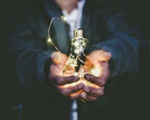 a man holding a lightbulb to symbolise creating content marketing