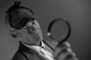 a man with a magnifying glass to represent doing your research for the partnership admissions process