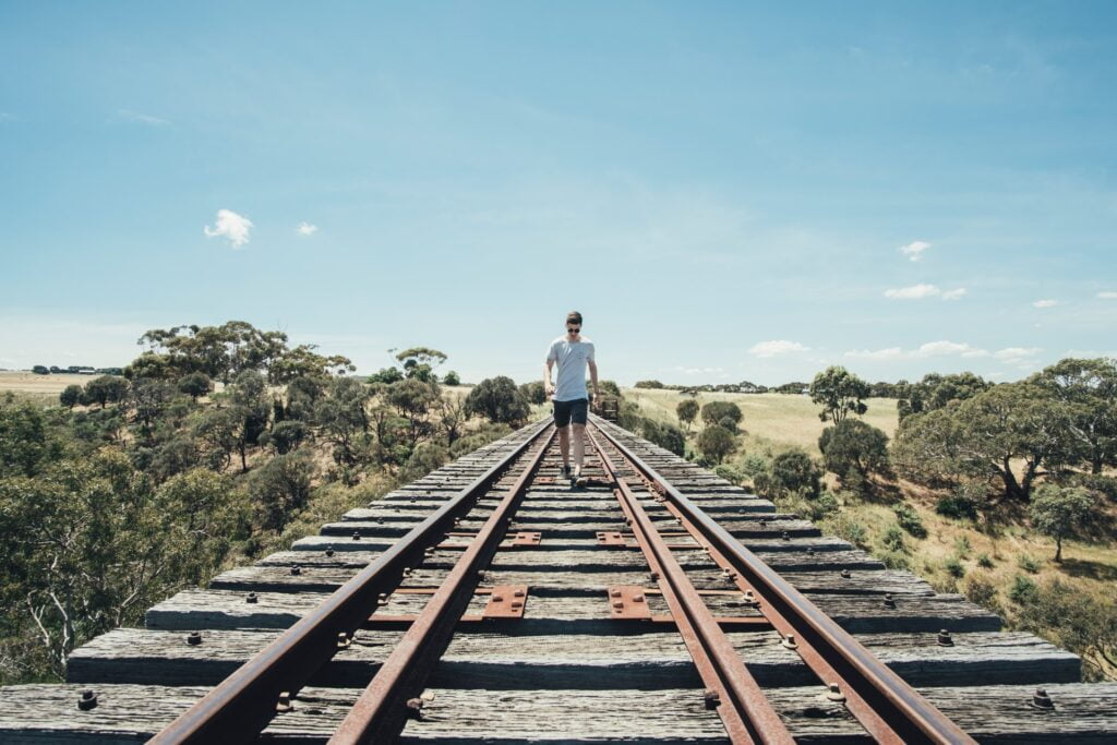 a man walking on train tracks to symbolise how to get put on the partner track
