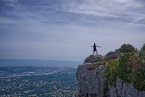 a woman standing on a mountain with outstretched arms to symbolise ambition