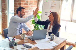work colleagues high fiving to represent office politics when moving your career forward