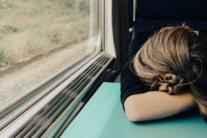 a woman sleeping on a train to represent burning out