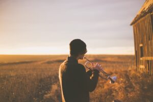 a man playing a trumpet to represent self-promotion